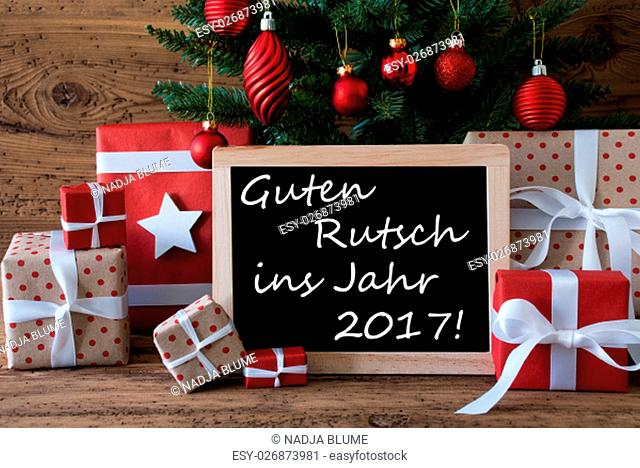 Colorful Card For Seasons Greetings. Christmas Tree With Red Balls. Gifts Or Presents In The Front Of Wooden Background. Chalkboard With German Text Guten...
