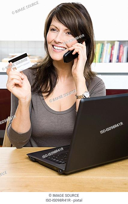 Woman with cellphone credit card and laptop