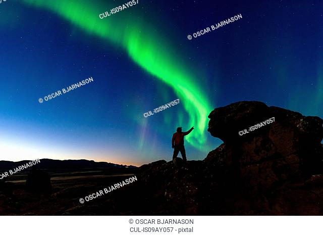 Man standing on rocks, watching Northern Lights, Krysuvik, Iceland