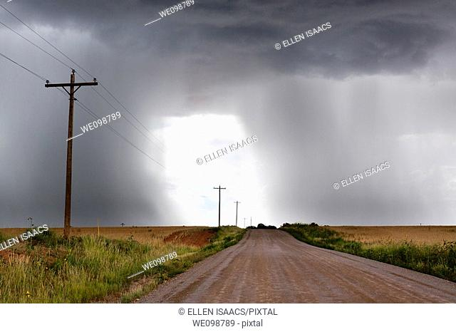 Rural thunderstorm scene showing dirt road leading to a bright light opening up between looming cumulus thunder clouds releasing rain