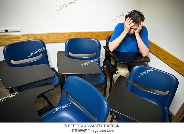 Man, holding onto his head with his hands, sitting in his student desk in an otherwise empty college classroom
