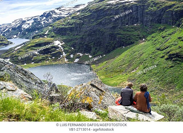 Hikers resting atop a cliff near Osterbo, Norway