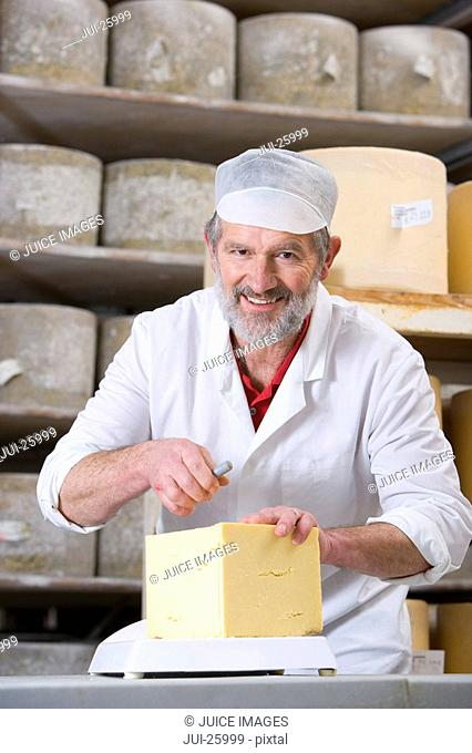Portrait of smiling cheese maker cutting farmhouse cheddar with cheese wire in cellar