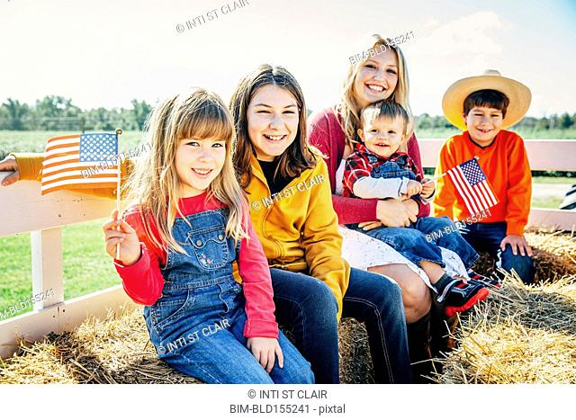 Caucasian mother and children waving American flags on hay ride