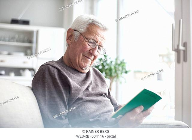 Portrait of senior man sitting on couch at home reading a book