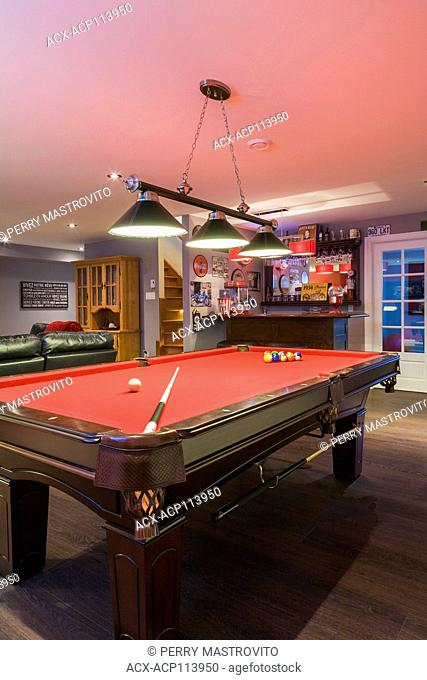 Pool table and bar in the family room in the basement inside a contemporary country style residential home, Quebec, Canada