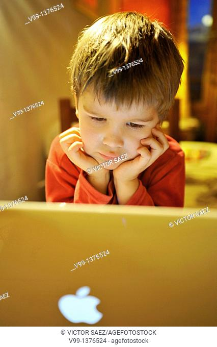 young boy who watches a movie on computer