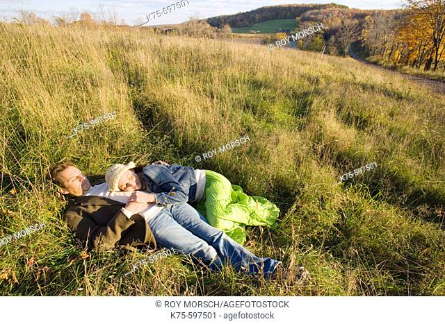 Couple lying in field in the sunshine