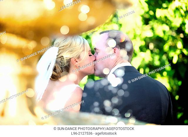 happy couple kissing behind the fountain
