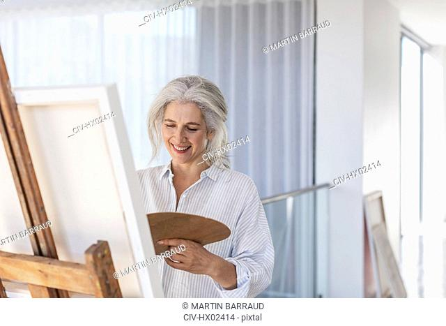 Smiling mature woman with palette painting at canvas on easel