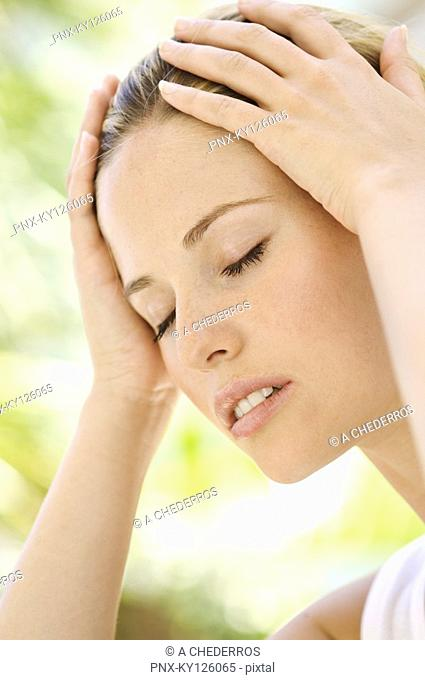 Portrait of a young woman, eyes shut, hands on her head, outdoors