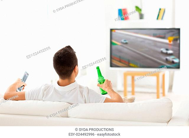 sport, leisure, technology, motorsports and people concept - man watching car racing on tv and drinking beer from bottle at home from back