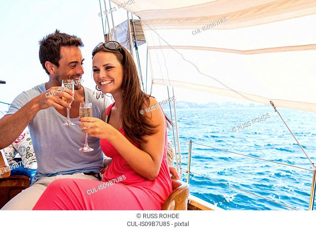 Couple sitting on boat, on water, holding champagne flutes, smiling