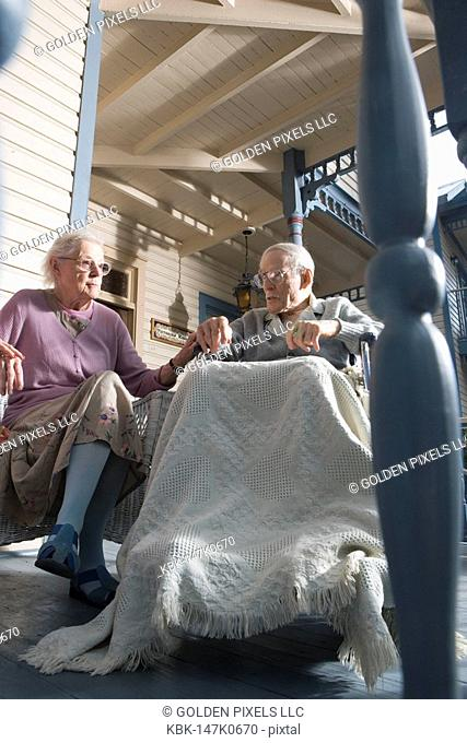 Senior couple sitting together on front porch