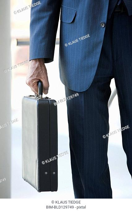 Senior Caucasian businessman carrying briefcase