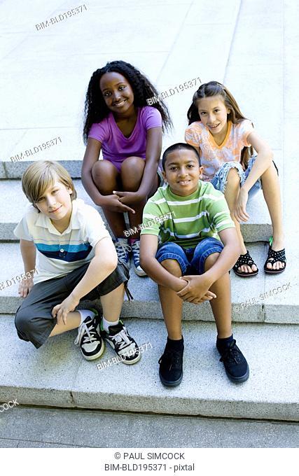 Smiling children sitting on steps together