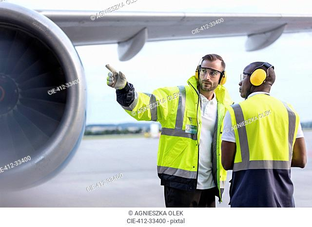 Air traffic control ground crew workers talking near airplane on airport tarmac