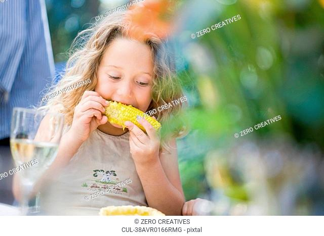 Girl eating corn at table outdoors