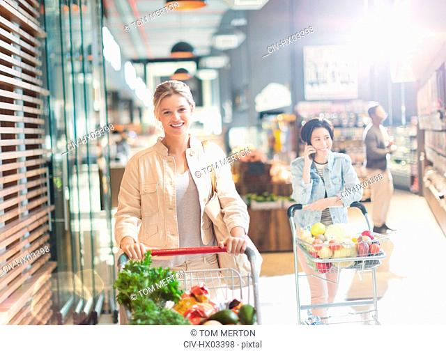 Portrait smiling young woman with shopping cart in grocery store market