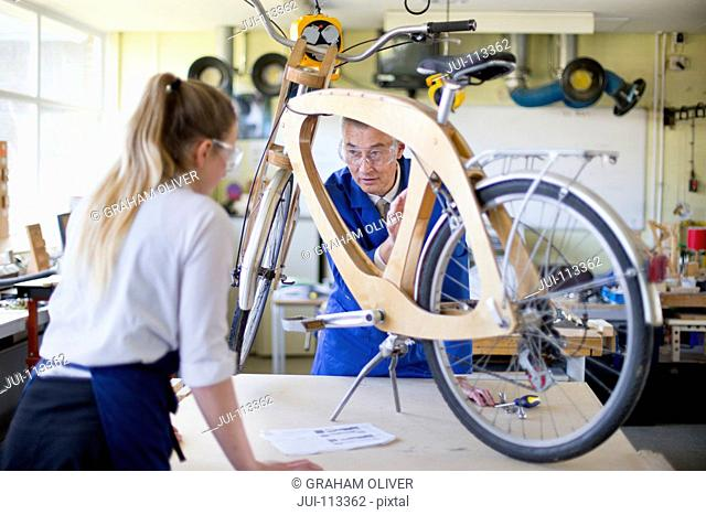 Teacher and female high school student assembling bicycle in woodworking class