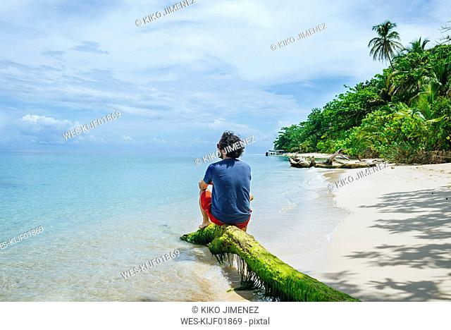 Panama, Bocas del Toro, Cayo Zapatilla, Man sitting on tree trunk on the beach