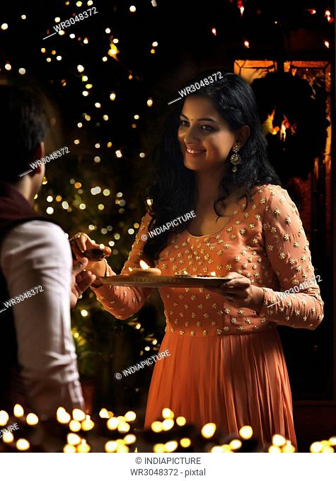 Young couple holding oil lamps in a plate on diwali