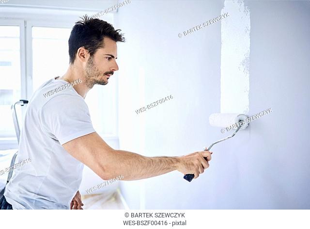 Man painting wall in apartment