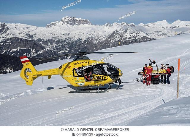 Injured skier is transported by snowmobile in rescue helicopter ÖAMTC, Silvretta Montafon, Kapellalpe, village of Schruns, Montafon, Vorarlberg, Austria