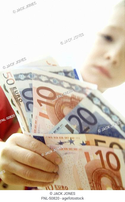 Close-up of boy holding banknotes