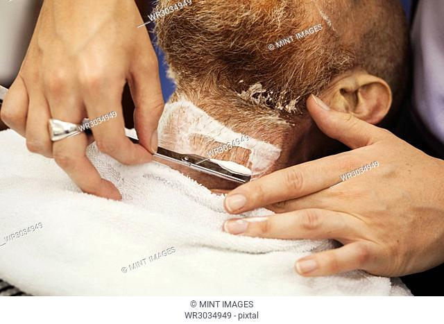 A customer sitting in the barber's chair, having a wet shave by a barber using a cut throat razor