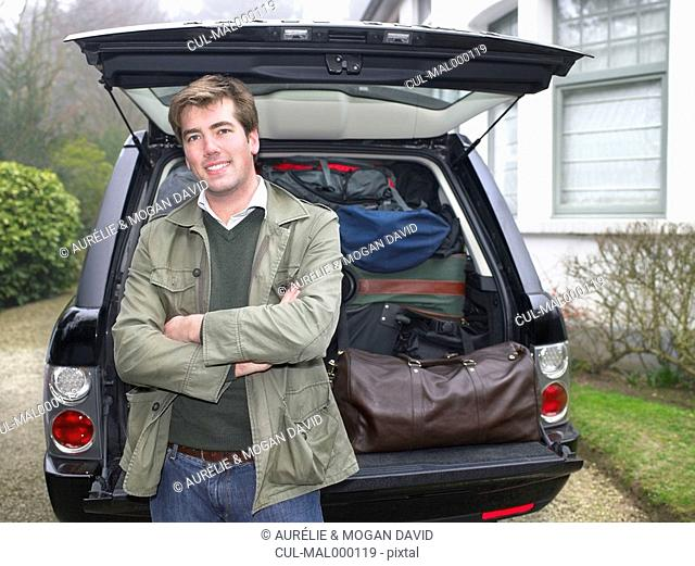 Young man in front of packed car