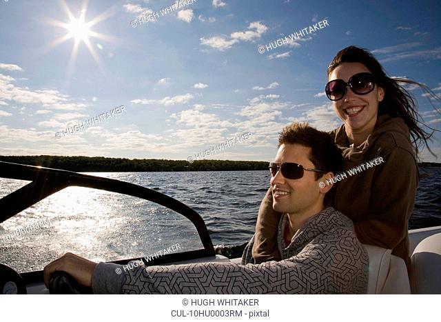 Couple driving speedboat on lake
