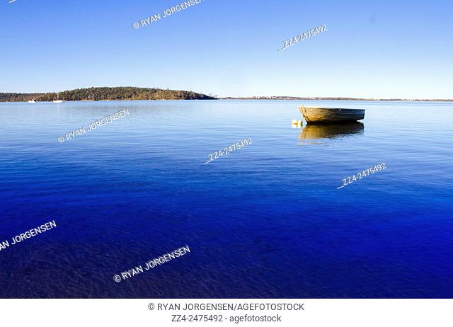 Small motor boat floating on a bright blue ocean. Boating backgrounds