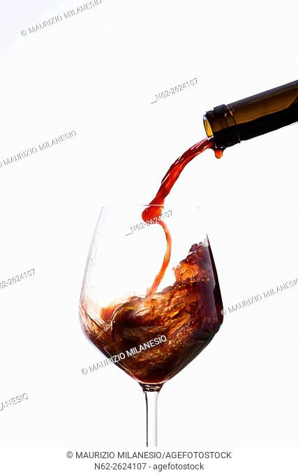 Vigorously wine poured from a bottle in a wine glass, on a white background