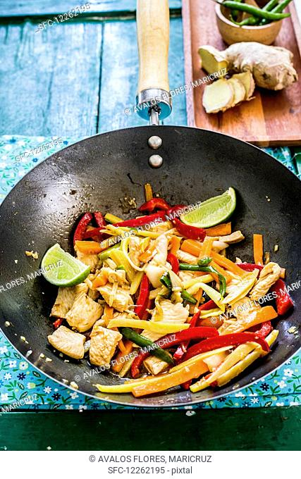Chicken with ginger and vegetables in a wok (Asia)
