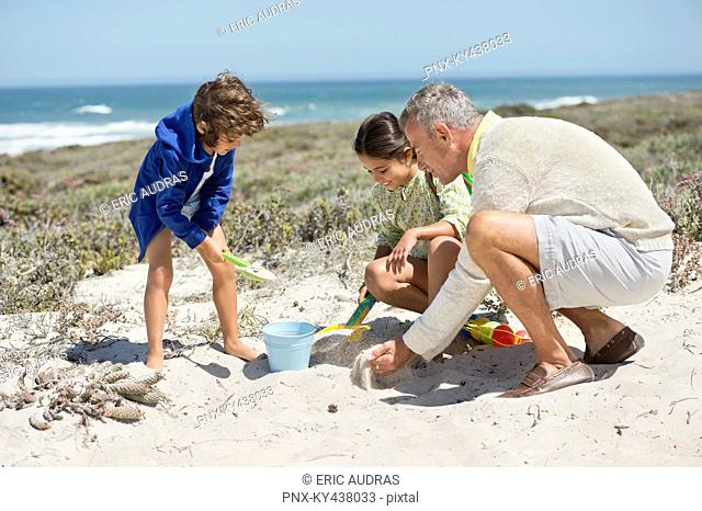 Children playing in sand with their grandfather on the beach