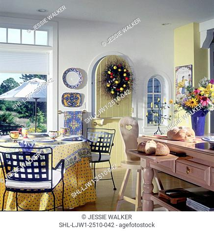 KITCHENS: Breakfast area, yellow Dutch door to patio, Country French pattern tablecloth, metal chairs, sliced bread on center island, vase of flowers