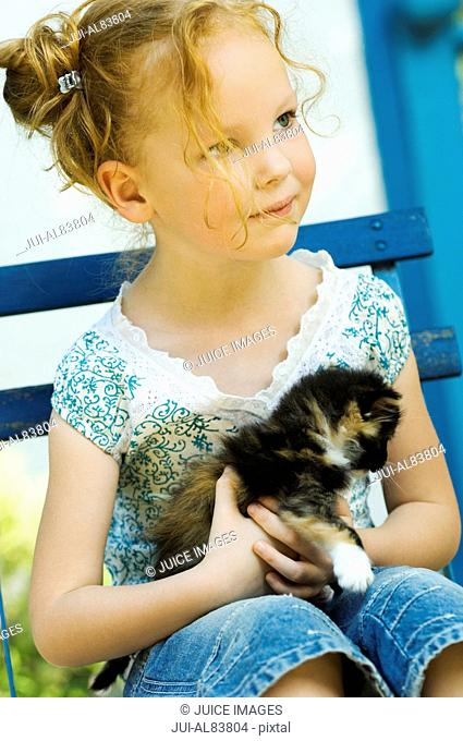 Young girl sitting in chair with kitten outdoors