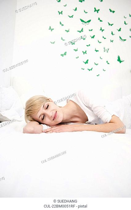 Young woman resting on bed smiling