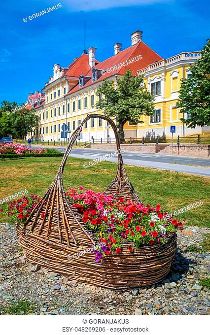 View of a large straw basket with flowers in a park with the City museum located in the Eltz castle in the background in Vukovar, Croatia