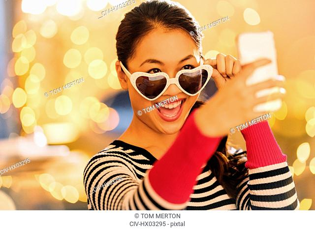 Playful Chinese woman wearing heart-shape glasses taking selfie with camera phone