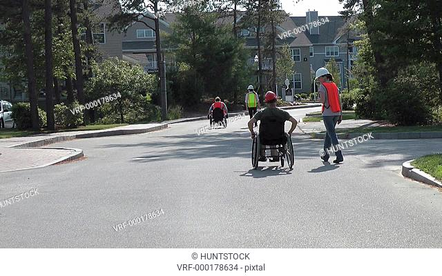 Construction engineers surveying new location, men in wheelchairs with spinal cord injuries