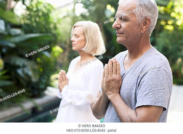 senior couple meditating together
