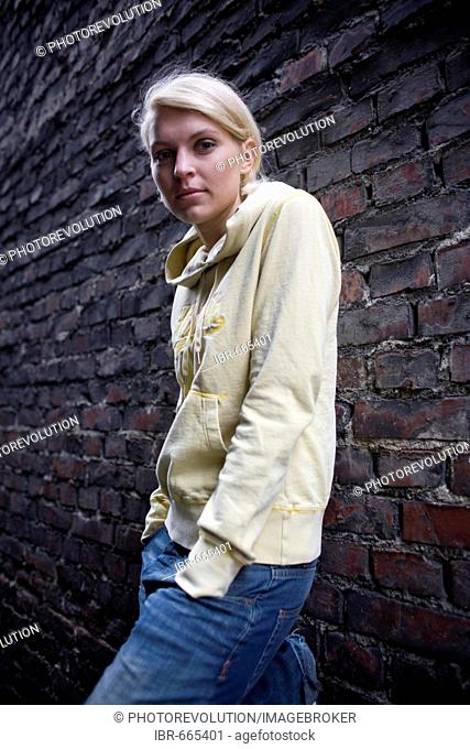 Blonde woman leaning against a brick wall