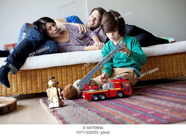 Boy playing with toys, mother and father lying on sofa in background