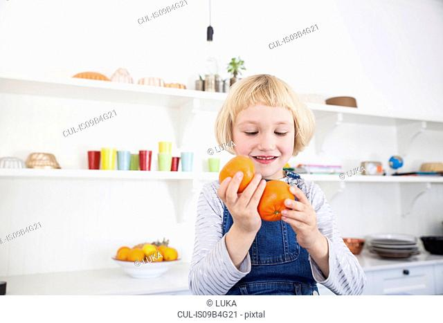 Cut girl looking at oranges in kitchen