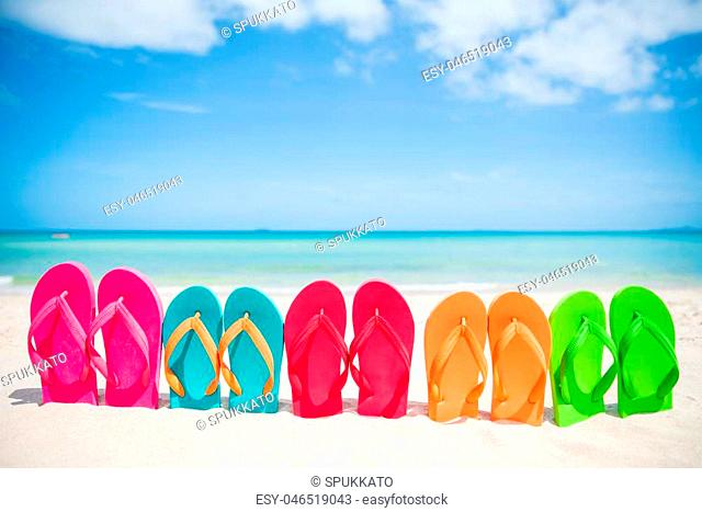 colorful flip flop on sandy beach, green sea and blue sky background for summer holiday and vacation concept