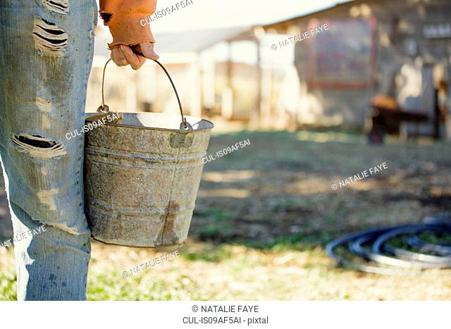 Farmer holding metal bucket, close-up