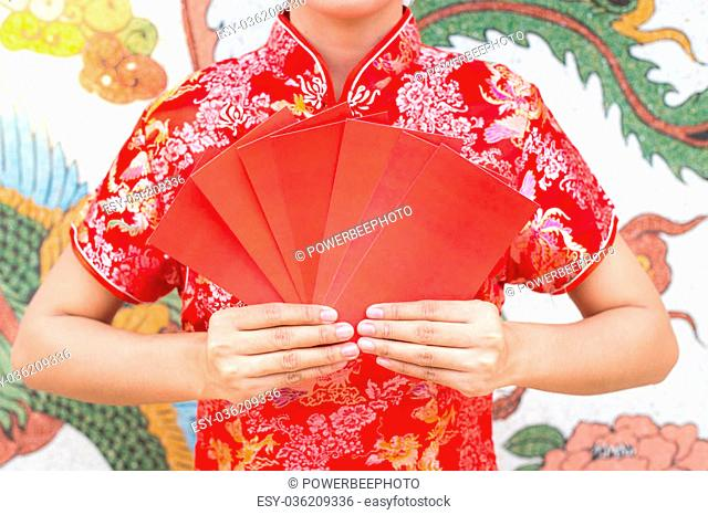 Happy chinese new year,Asian woman dress traditional cheongsam and qipao holding red envelopes ang pow or red packet monetary gift card on chinese pattern...
