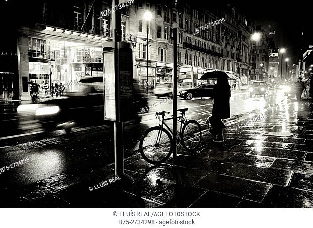 Street scene, rain, bus stop, taxis, bicycle, unrecognizable woman with umbrella. Piccadilly, London, England